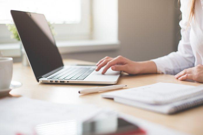 Kvinde arbejder på sin computer med notesbog