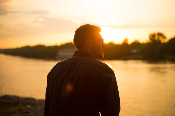Mand står og kigger ud mod solnedgang over sø